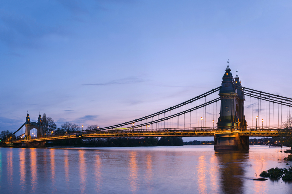 Hammersmith Bridge at dusk, stretching over the Thames