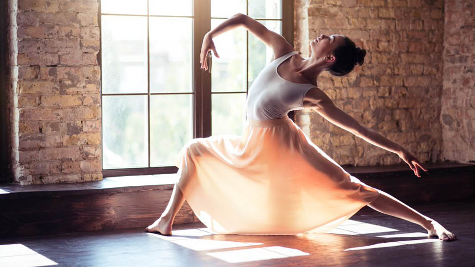A ballet dancer strikes a pose, backlit in front of a window