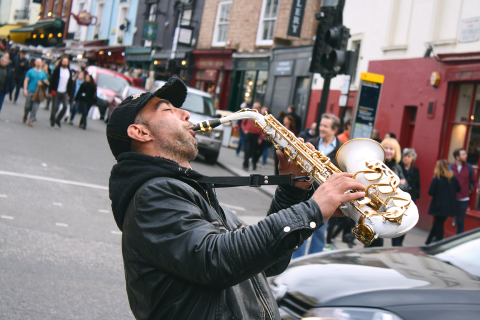 A saxophonist plays to weekend shoppers in fashionable Notting Hill