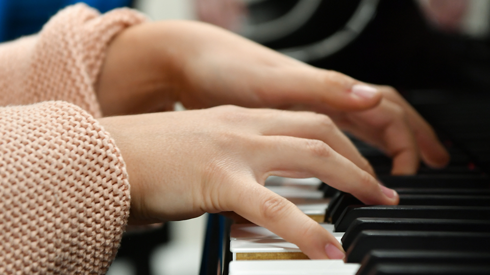 A pianists fingers on the keys of the instrument