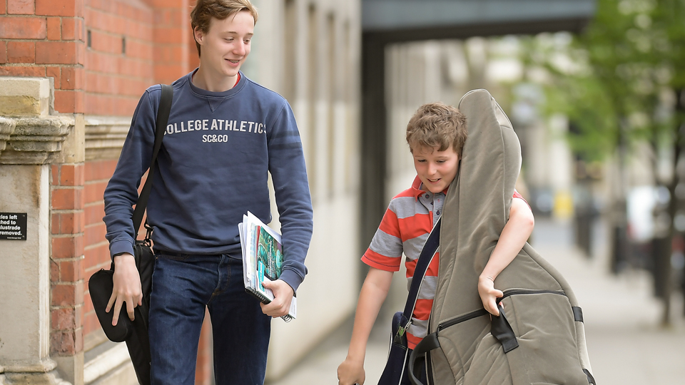 Two Junior Department students, one carrying a double bass, arrive at College