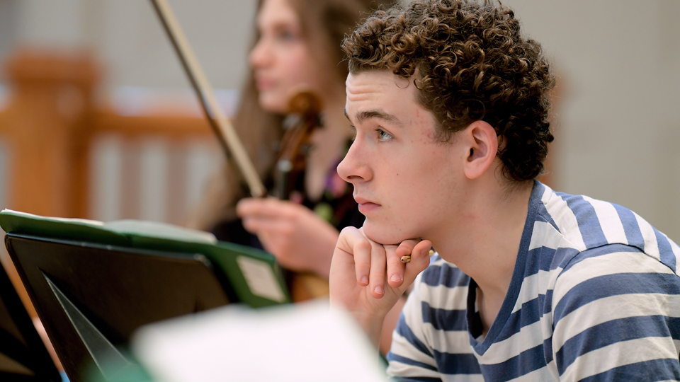 A Junior Department student listening during a rehearsal