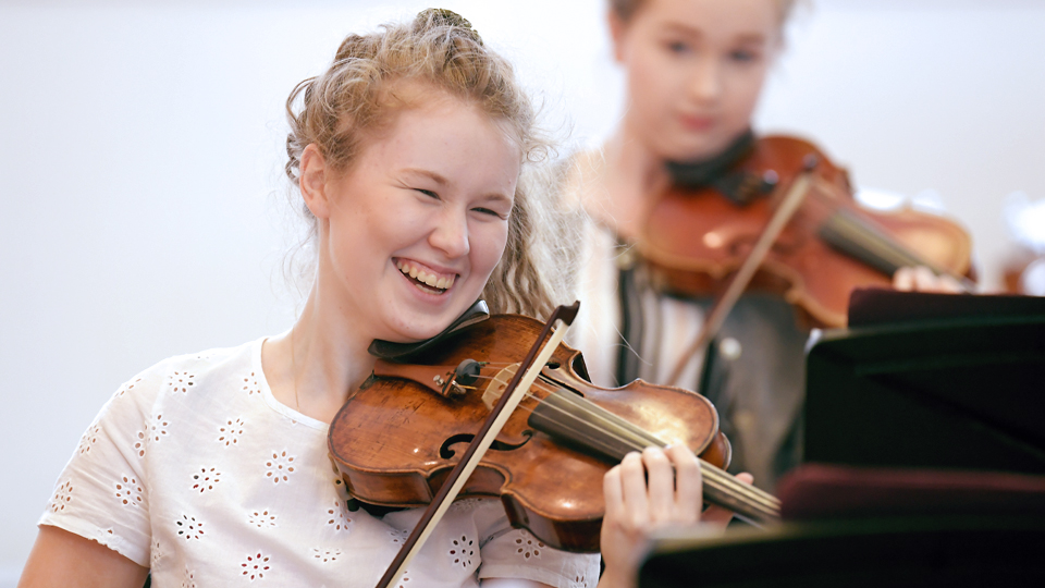 A Junior Department violinist enjoying a rehearsal