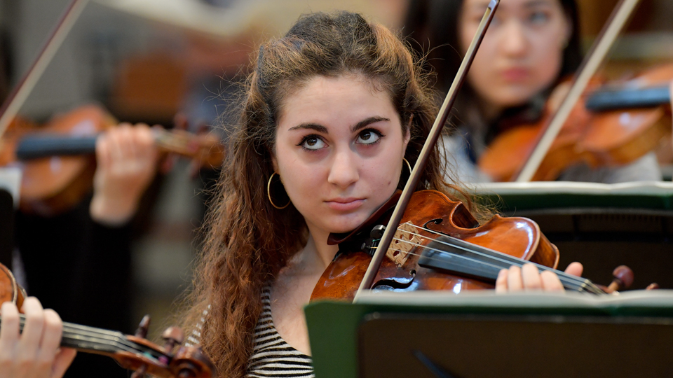 A Junior Department violinist in an orchestra rehearsal