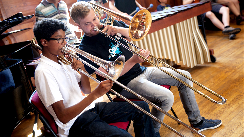 Trombonist with a mentor at an RCM Sparks event