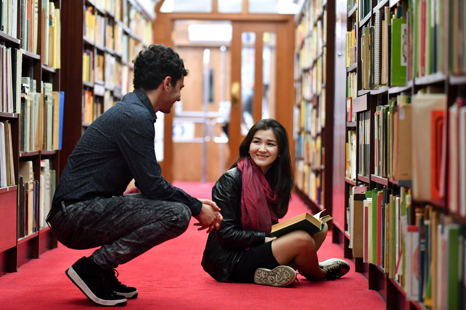 Students chatting while looking through shelves in the RCM Library