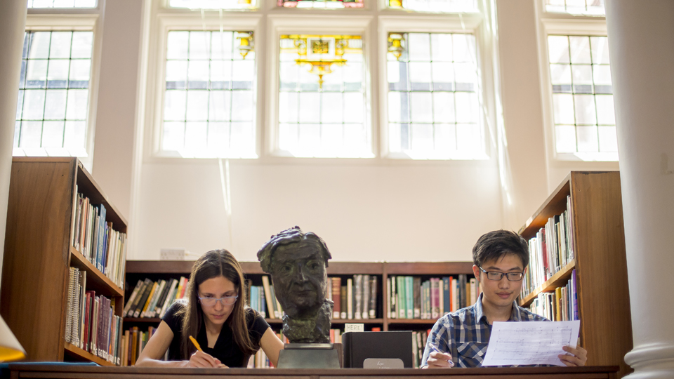 Students working beneath stained glass windows in the Donaldson Room in the RCM Library