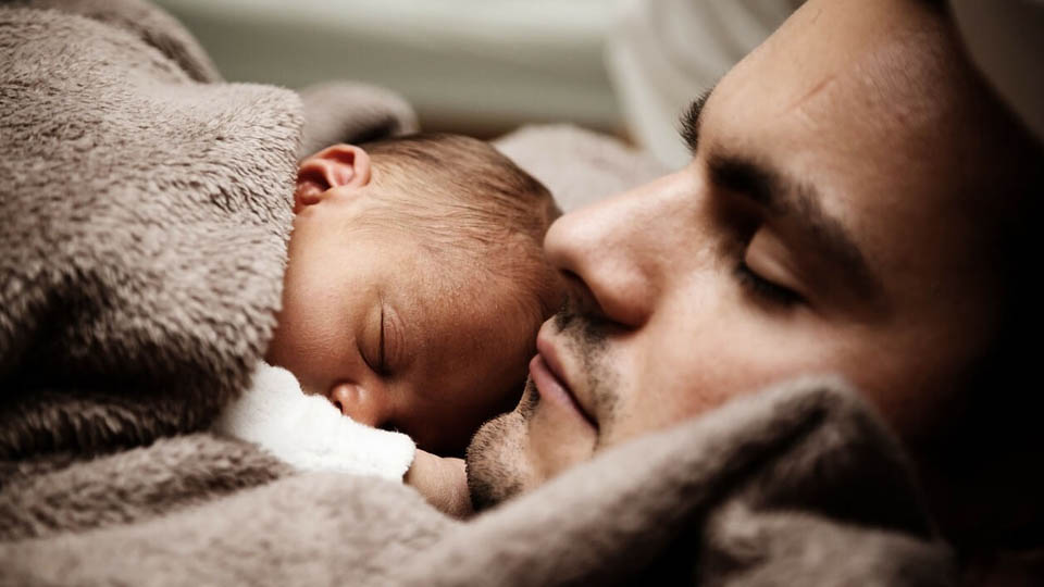 A man cradles a warmly wrapped baby as they both sleep
