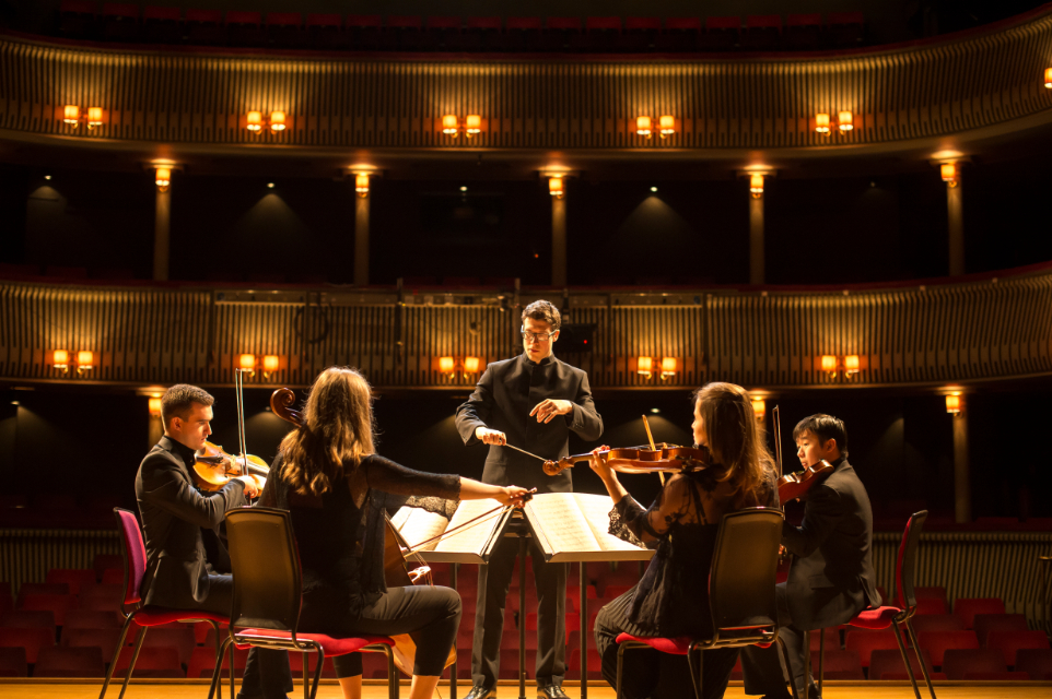 RCM student Mark Biggins conducts musicians on the Britten Theatre stage